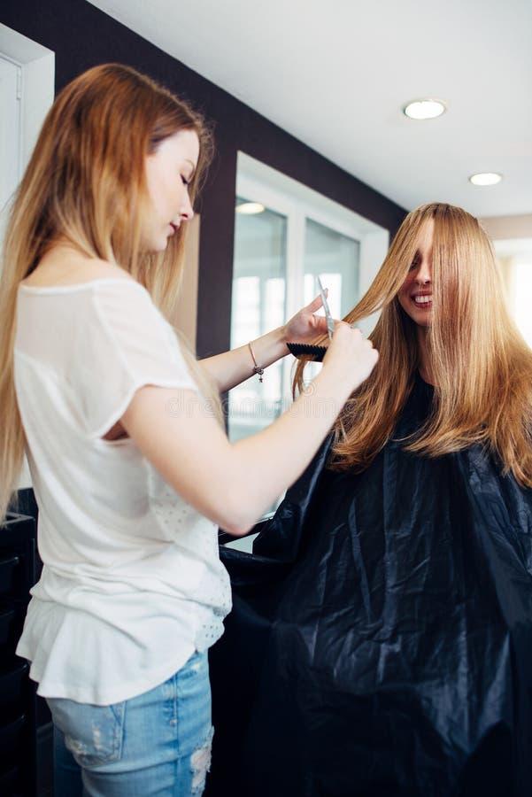 Frisören är förlovad, i att klippa kluvna hårtoppar av långt hår av positivt ungt kvinnligt klientsammanträde i udde och royaltyfri bild