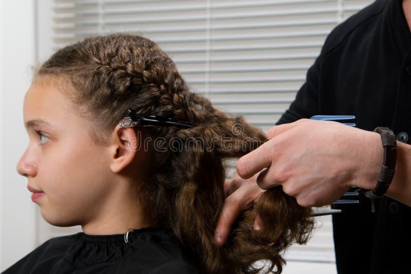 Frisören flätar en råttsvans till barnet, med lockigt hår och gör hairdress fotografering för bildbyråer