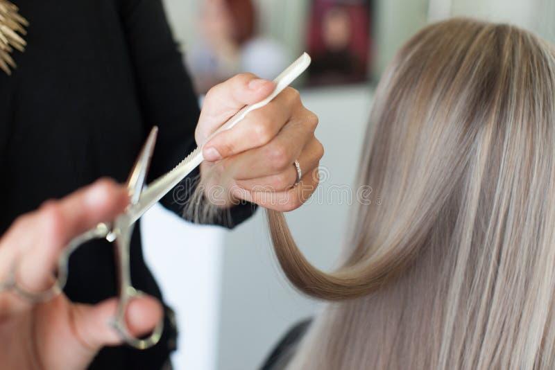 Frisören gör håret att klippa flickan med långt hår arkivfoto