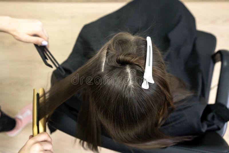 Frisören gör hårlamination i en skönhetsalong för en flicka med brunetthår arkivbilder