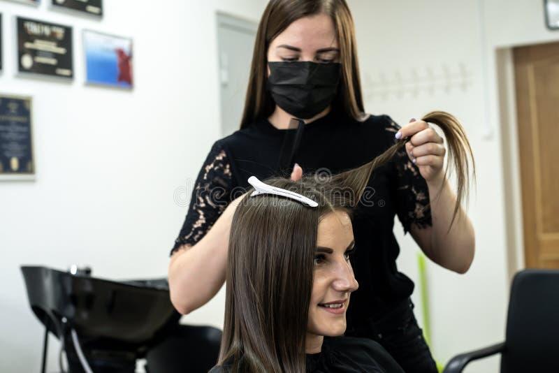 Frisören gör hårlamination i en skönhetsalong för en flicka med brunetthår Begrepp f?r h?romsorg royaltyfria bilder