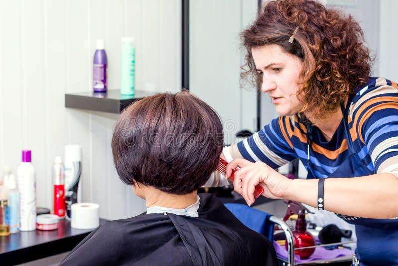 Frisören gör kvinnan den stilfulla frisyren Yrkesmässig hairdr arkivbild