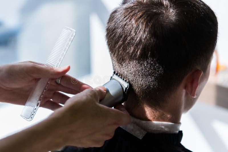 Frisören jämnar en frisyr med hjälpen av en rakapparat och en hårkam i en frisersalongnärbild royaltyfri foto