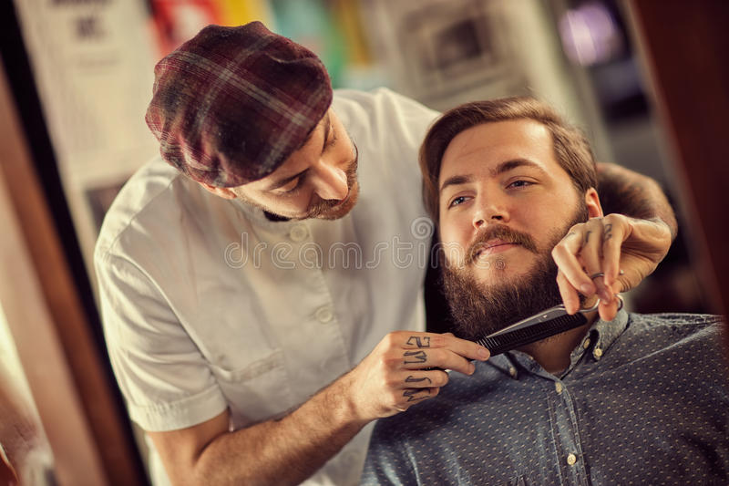 Frisören med den svarta hårkammen och sax klippte skägget royaltyfria bilder