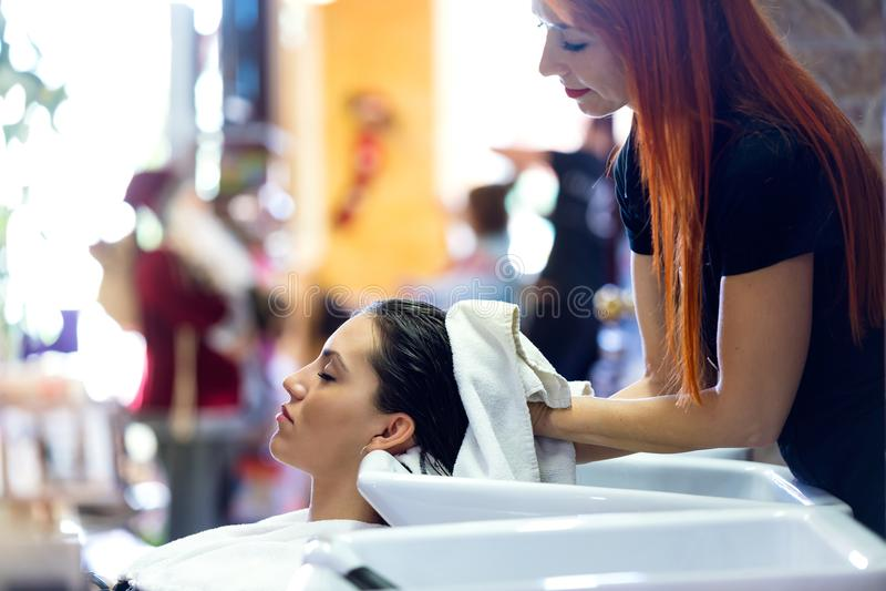 Frisören slår in håret för klient` s i en handduk, når han har tvättat sig royaltyfri bild