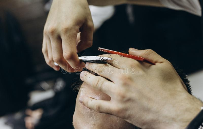 Fris?ren som g?r h?r i barberaren, shoppar med sax royaltyfri fotografi