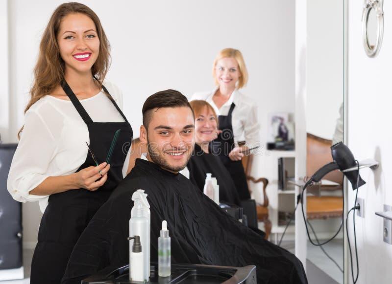 Frisörer och klienter i hårsalong royaltyfri bild