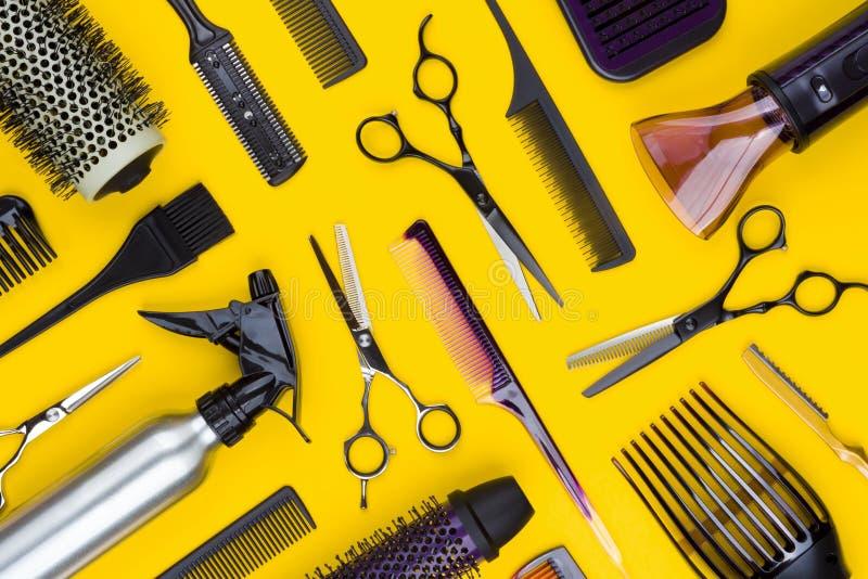Frisörhjälpmedel och hårkamhjälpmedel på gul bakgrund, bästa sikt royaltyfri fotografi