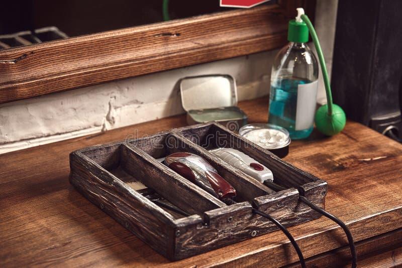 Frisörhjälpmedel på träbakgrund Bästa sikt på trätabellen med sax, hårkammen, hårborstar och hairclips, beskärare arkivfoto