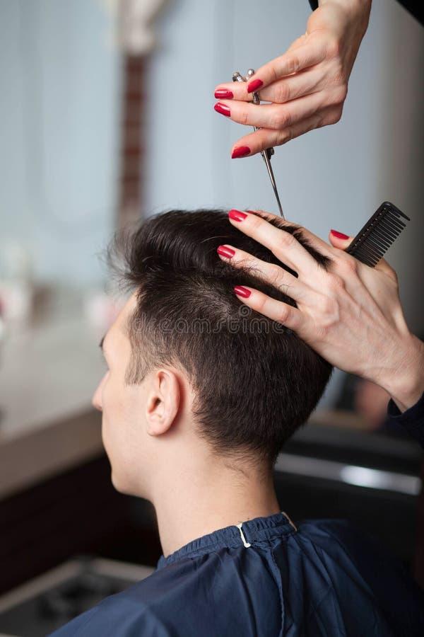 Frisörklippmans hår med sax royaltyfri foto