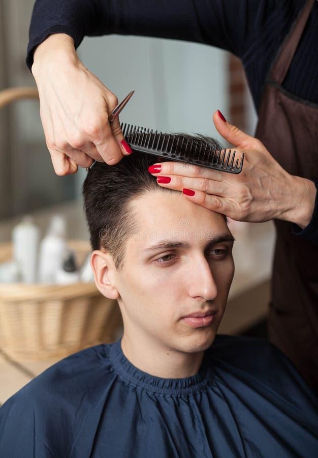 Frisörklippmans hår med sax fotografering för bildbyråer