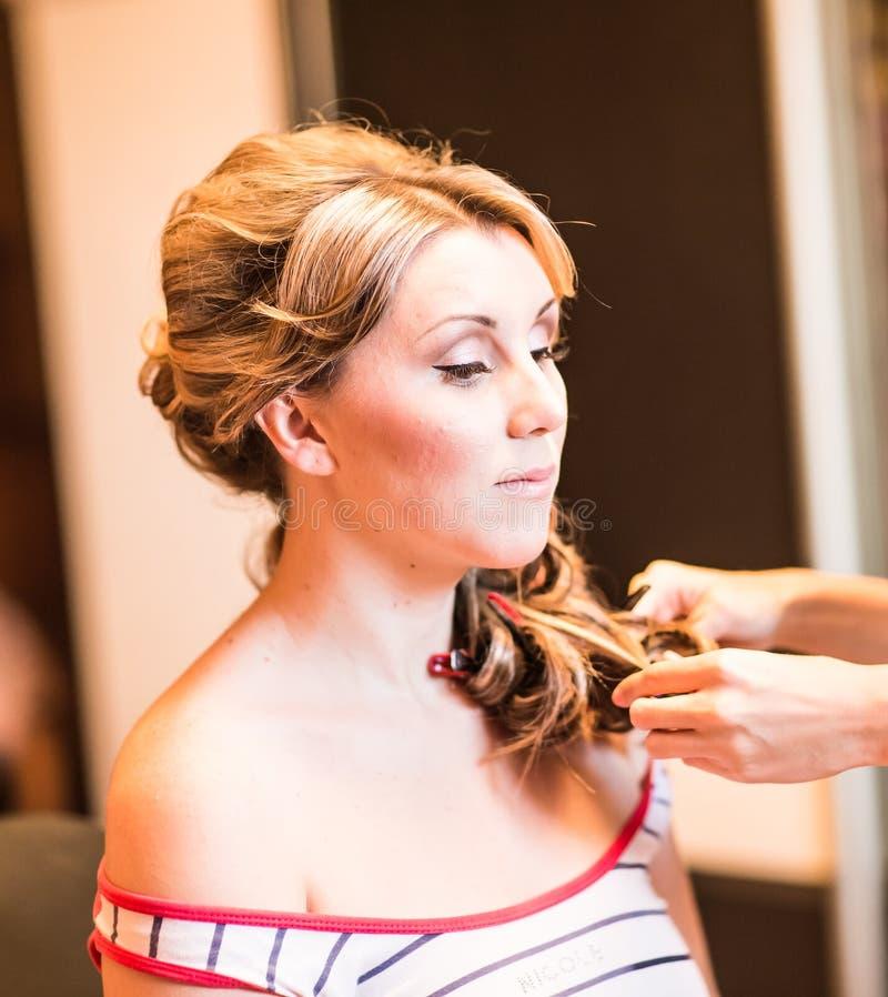 Frisörkvinnan krullar hennes hår royaltyfri fotografi