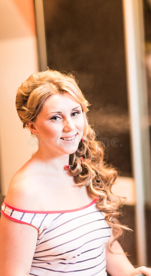 Frisörkvinnan krullar hennes hår arkivfoton