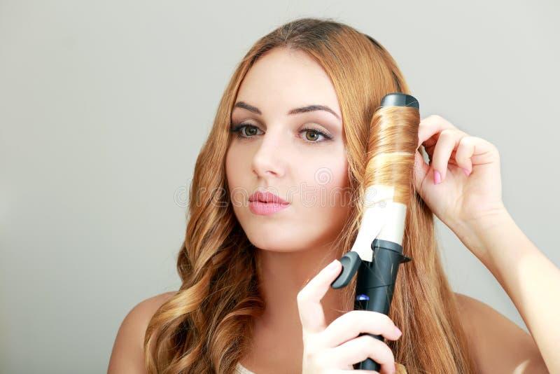 Frisörkvinnan krullar hennes hår royaltyfria bilder