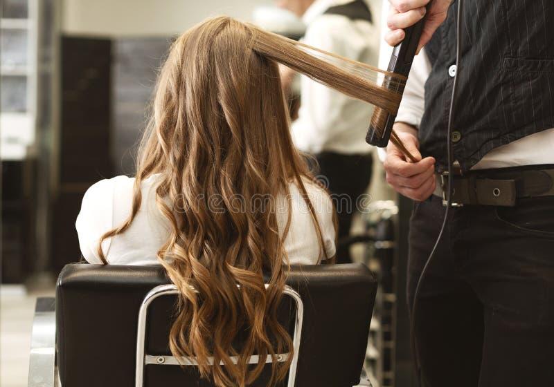 FrisörMaking Curls With Straightener till klients hår i salong arkivfoto