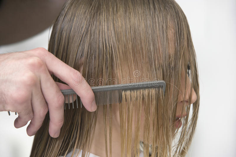 Frisörs hand som kammar klients hår i mottagningsrum royaltyfri foto