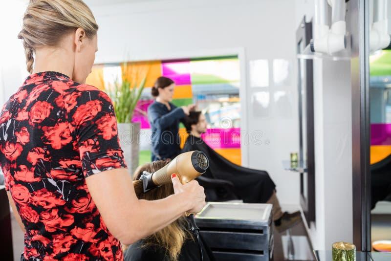 Frisöruttorkningkunds hår med slagtorken arkivfoto