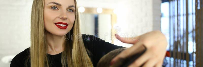 Fris?r Making Haircut f?r ung kvinna med h?rkammen royaltyfri foto