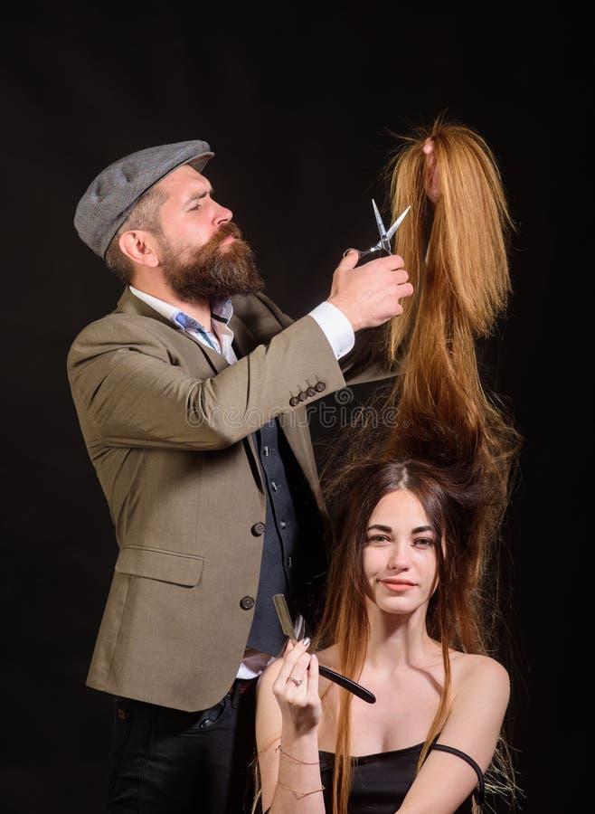 Fris?ren g?r frisyren en kvinna med l?ngt h?r Stående av den stilfulla kvinnamodellen Den ledar- fris?ren g?r frisyren royaltyfri fotografi