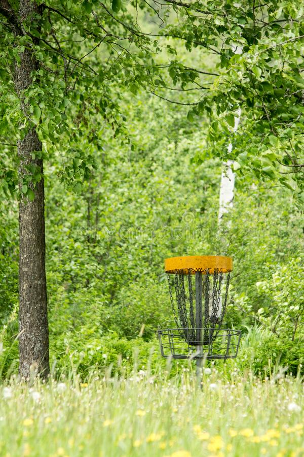 Frisbee golf basket behind blurred grass in the middle of leafy tree forest stock photo