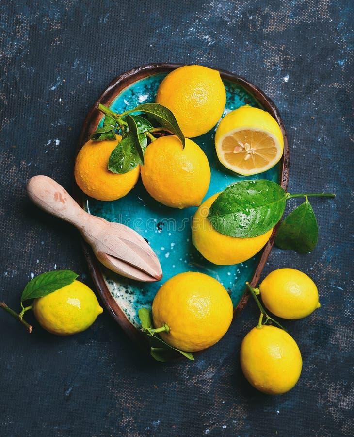 Frisch ausgewählte Zitronen mit Blättern in der blauen keramischen Platte stockfotos