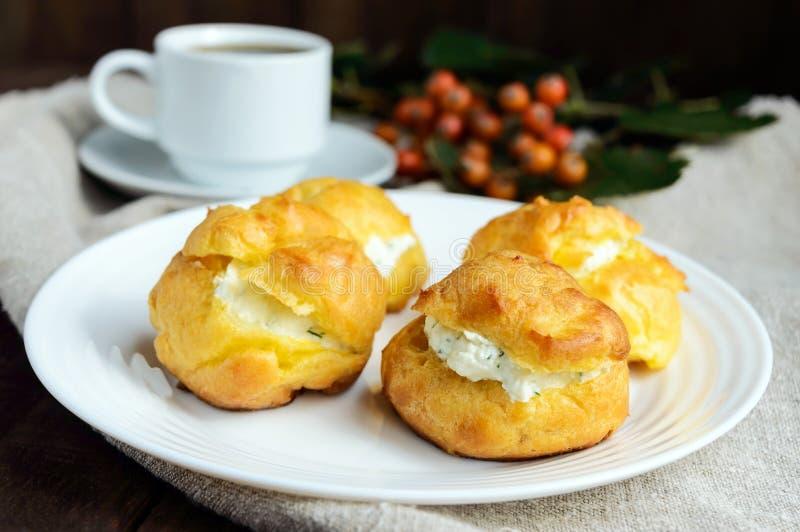 Frisch gebackene Brötchen Eclairs angefüllt mit würzigem Hüttenkäse und ein Tasse Kaffee u. ein x28; Espresso stockfotos