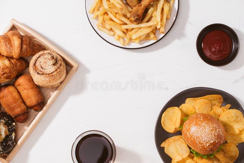 Frisch gebackene Brötchen, großer Hamburger, gebratenes knusperiges Huhn und Pommes-Frites auf weißer Tabelle - ungesundes Nahrun lizenzfreie stockbilder