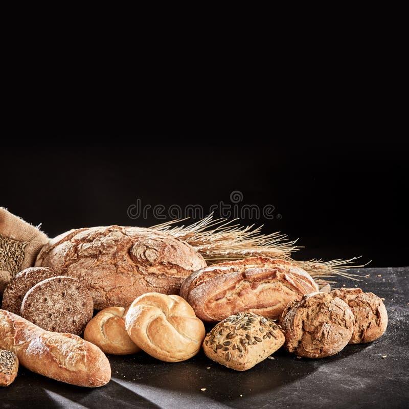 Frisch gebackene Brotzusammenstellung auf Schwarzem stockbild