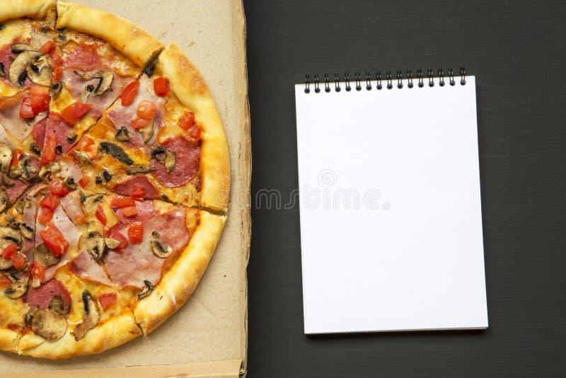 Frisch gebackene Pizza in einer Pappschachtel mit Notizbuch über schwarzem Hintergrund, Draufsicht stockfoto