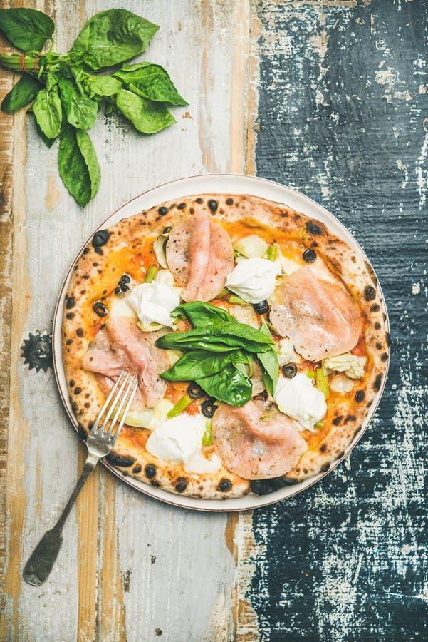 Frisch gebackene Pizza mit Schinken, Artischocken, Käse, Basilikum auf Platte lizenzfreie stockbilder