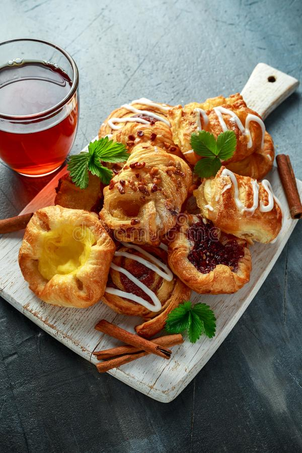 Frisch gebackene süße mini dänische klebrige Ahornpekannuß des traditionellen Gebäcks, Zimt, Apple, Himbeermischung mit heißem lizenzfreies stockbild