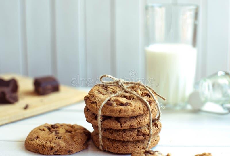 Frisch gebackene Schokoladensplitterplätzchen mit Glas Milch auf rustikalem Holztisch lizenzfreie stockfotos