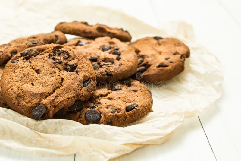 Frisch gebackene selbst gemachte Pl?tzchen der Schokolade auf Pergamentpapier mit einem wei?en Holztisch stockbilder