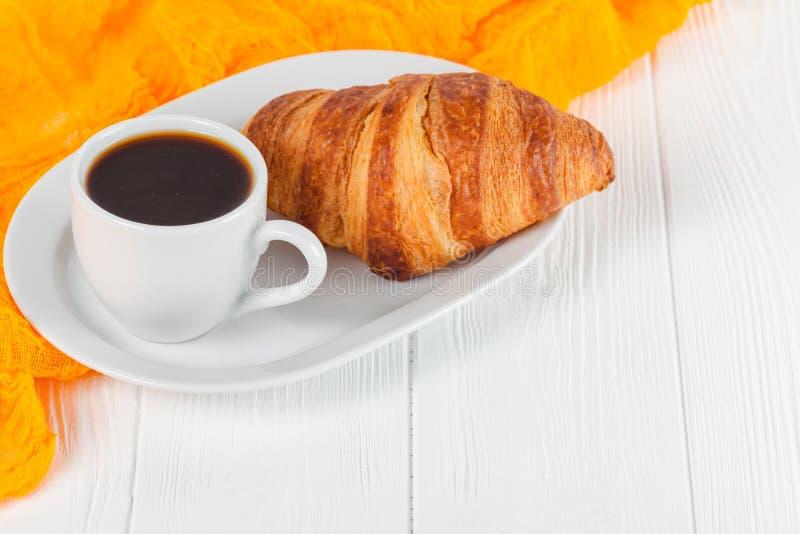 Frisch gebackener Orangensaft des Hörnchens, Stau, Schale schwarzer Kaffee auf weißem hölzernem Hintergrund Frisches Gebäck des f stockbilder