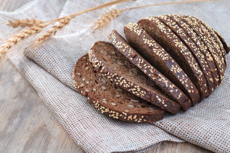 Frisch gebackenes Brot mit den Ohren des Roggens und des Weizens auf dem hölzernen BAC lizenzfreie stockfotos