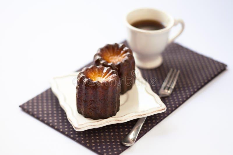 Frisch gebackenes cannele mit einem Tasse Kaffee lizenzfreie stockfotografie