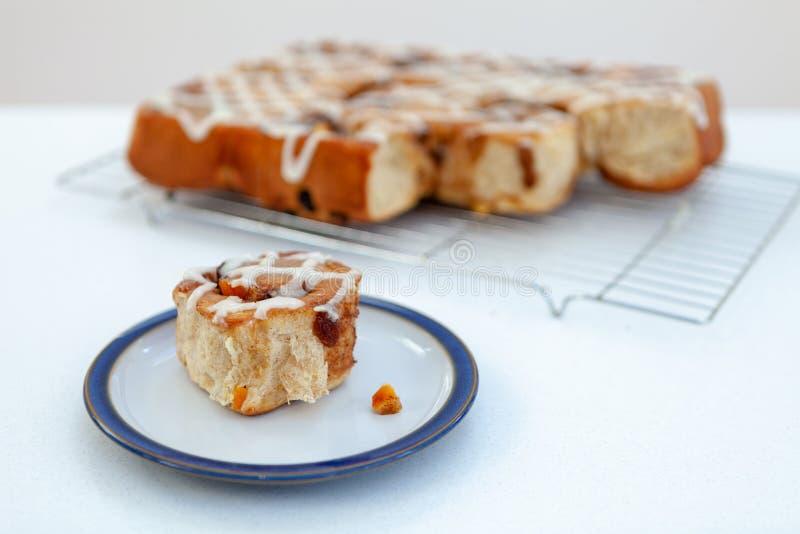 Frisch gebackenes Chelsea-Brötchen auf einer Platte mit mehr auf einem Draht coolin stockbilder