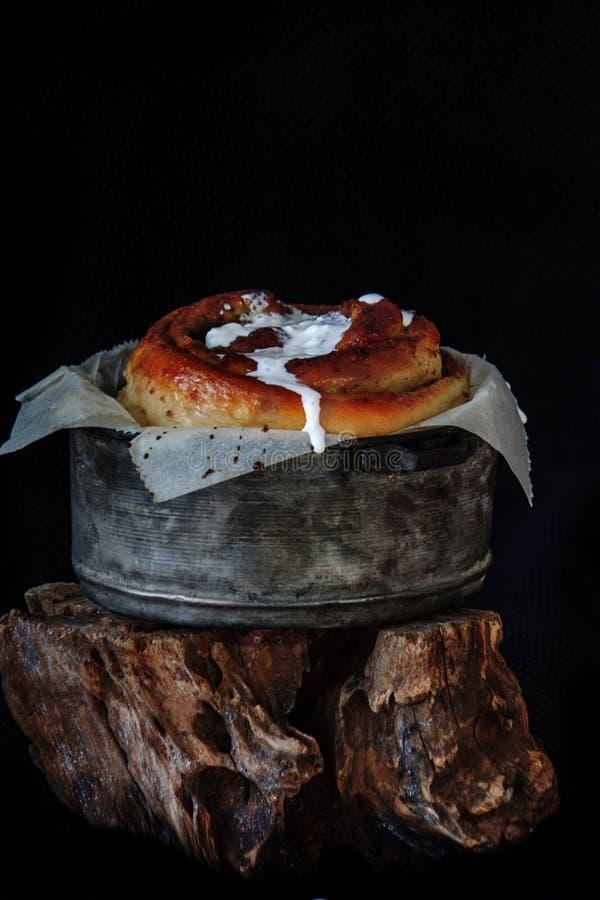 Frisch gebackenes großes Zimtbrötchen mit Zuckerglasur in einer Wanne mit Mohnblumen- und Kakaofüllung auf Pergamentpapier Süßes  lizenzfreies stockbild