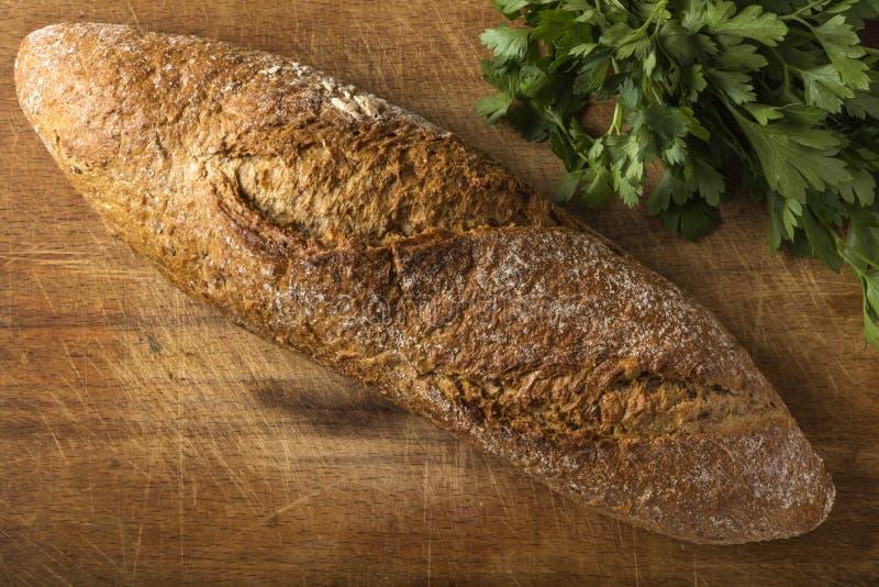 Frisch gebackenes selbst gemachtes Brot mit Bündel Petersilie lizenzfreies stockbild