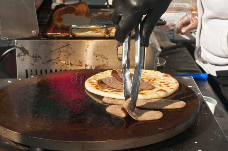 Frisch gebackenes, selbst gemachtes, griechisches flaches Brot auf einem heißen Grill und Scheiben des Bräts mit vendders griling lizenzfreies stockfoto