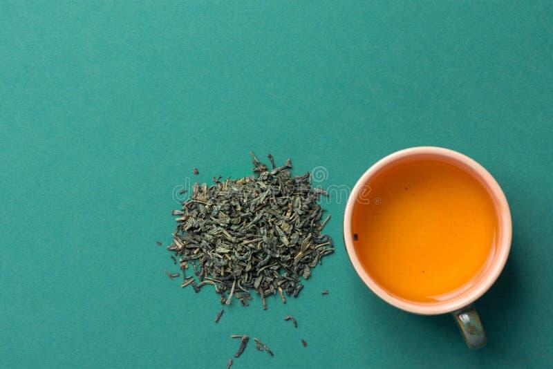 Frisch gebrauter grüner Tee in der keramischen Schale Einlegeblätter zerstreut auf festen dunklen Hintergrund Chinesische japanis lizenzfreie stockbilder