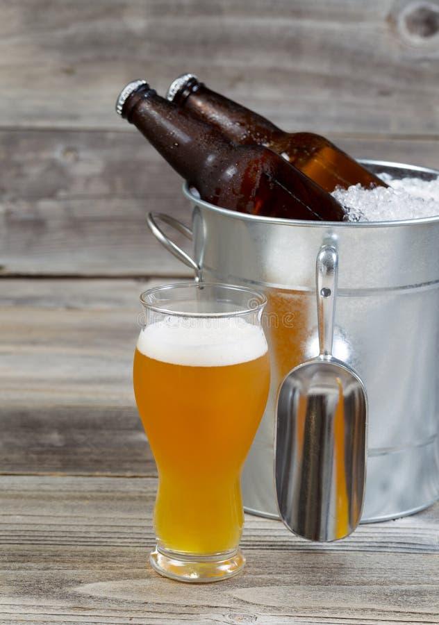 Frisch gegossenes Bier im Glas mit vollen Extraflaschen im backgrou stockbild