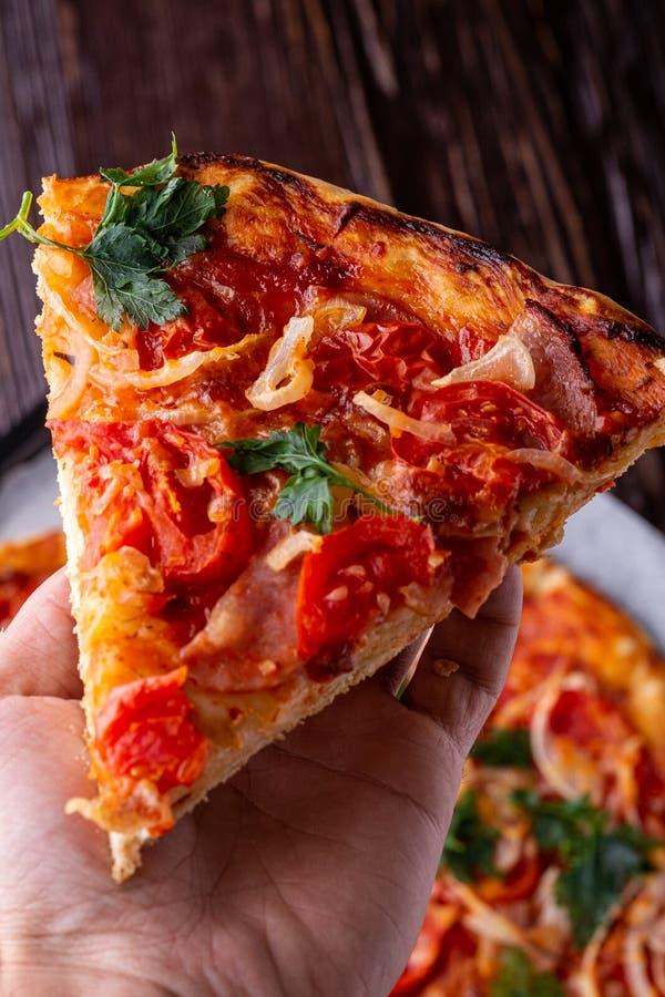 Frisch gekochte heiße Pizzascheibe, die in der menschlichen Hand mit selbst gemachtem Makro der Käseschinkenfleischtomatenzwiebel stockbild