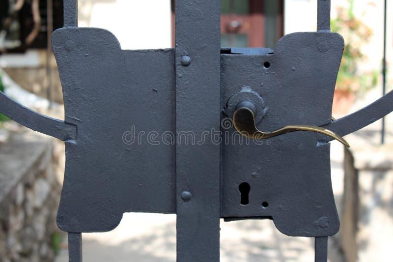 Frisch gemaltes Metalltürschloss auf starken Hinterhoftüren mit Poliertürgriff und großem Verschluss stockfoto