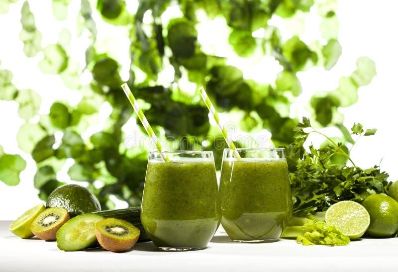 Frisch gemischter grüner Smoothie in den Gläsern mit Strohen Grün lässt Hintergrund lizenzfreie stockfotos