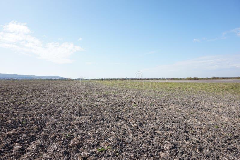 Frisch gepflogenes Feld und verlassene Straße europa stockbild