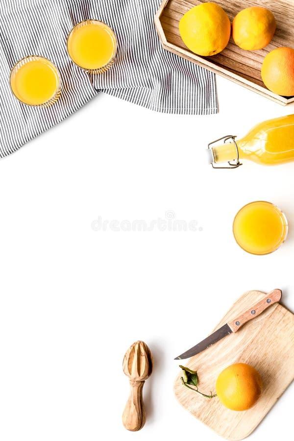 Frisch zusammengedrückter Orangensaft Juicer und Scheiben von Orangen auf weißem copyspace Draufsicht des Hintergrundes stockfoto