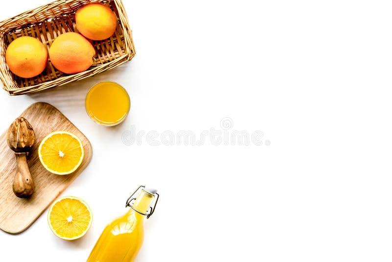 Frisch zusammengedrückter Orangensaft Juicer und Scheiben von Orangen auf weißem copyspace Draufsicht des Hintergrundes lizenzfreie stockfotos
