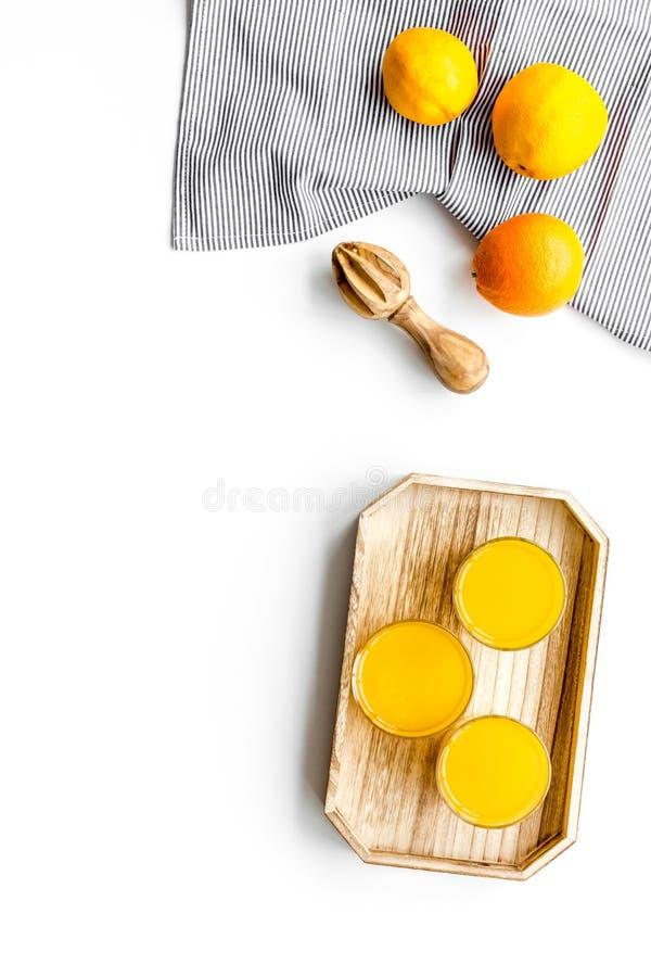 Frisch zusammengedrückter Orangensaft Juicer und Scheiben von Orangen auf weißem copyspace Draufsicht des Hintergrundes stockfotografie