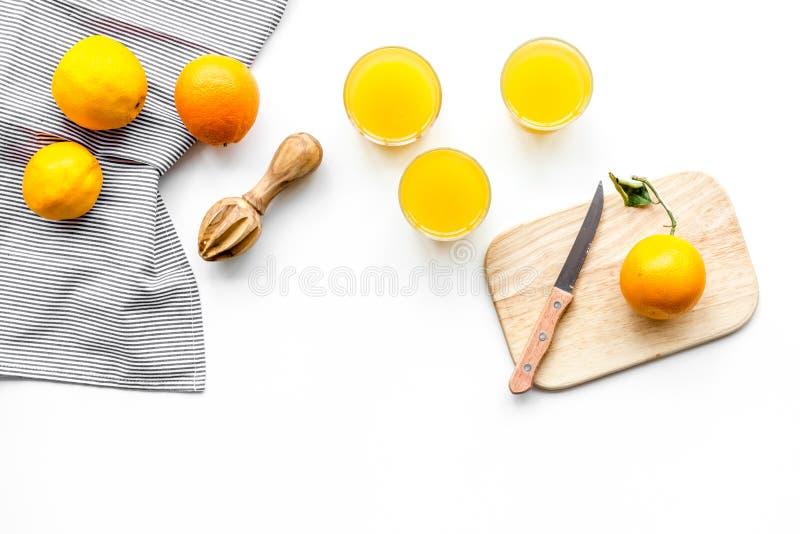 Frisch zusammengedrückter Orangensaft Juicer und Scheiben von Orangen auf weißem copyspace Draufsicht des Hintergrundes lizenzfreies stockbild